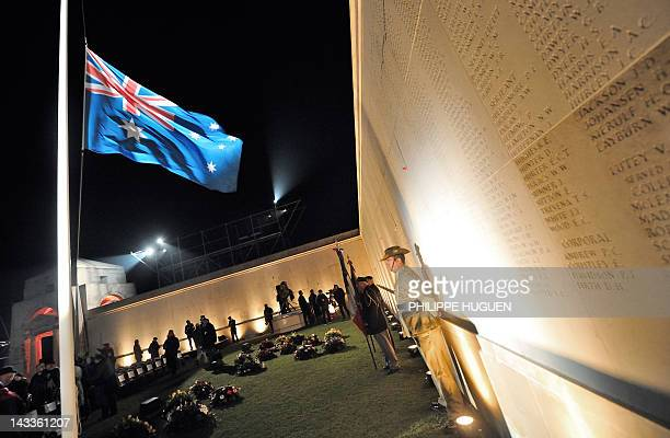 Australian soldiers stand in front of a wall bearing the WWI dead soldiers' names as they attend a dawn service at the Australian War Memorial in the...