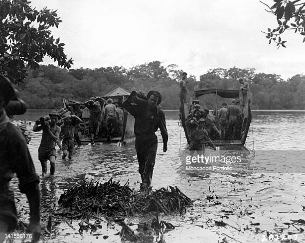 Australian soldiers unloading ammunition from two transport boats on the island of Sagakarsa Sagakarsa July 1943