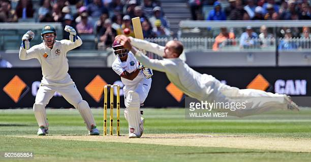 Australian spinner Nathan Lyon dives in an attempt to catch West Indies batsman Rajendra Chandrika as wicketkeeper Peter Nevill looks on on the...