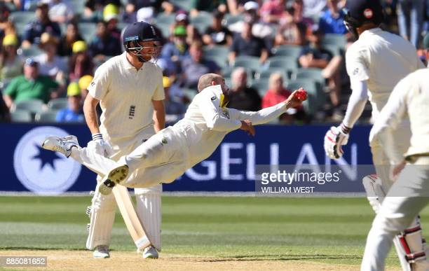 Australian spinner Nathan Lyon dives to take a catch to dismiss England batsman Moeen Ali as fellow batsman Jonny Bairstow looks on on the third day...