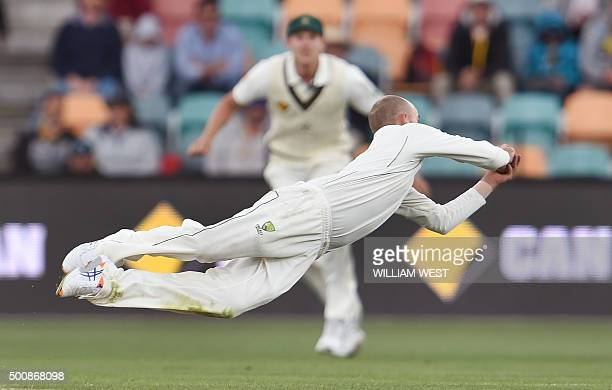 TOPSHOT Australian spinner Nathan Lyon dives to take a catch to dismiss West Indies batsman Marlon Samuels on the second day of the first cricket...