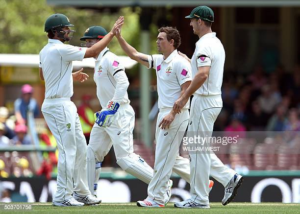 Australian spinner Stephen O'Keefe is congratulated by teammates Joe Burns Mitch Marsh and Peter Nevill after dismissing West Indies batsman Denesh...