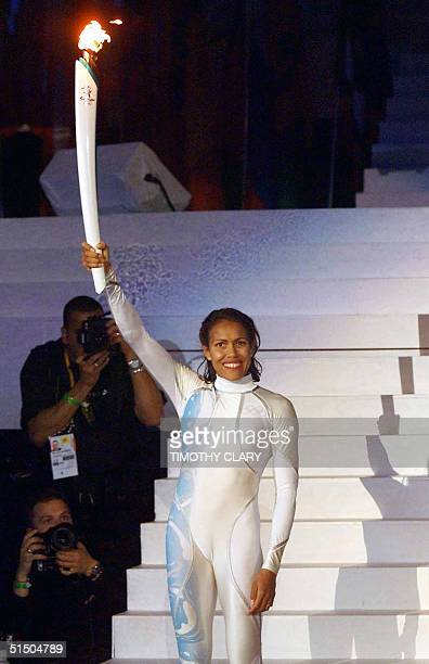 Australian sporting icon Cathy Freeman smiles as she displays the Olympic torch before lighting the Olympic cauldron 15 September 2000 in Sydney to...