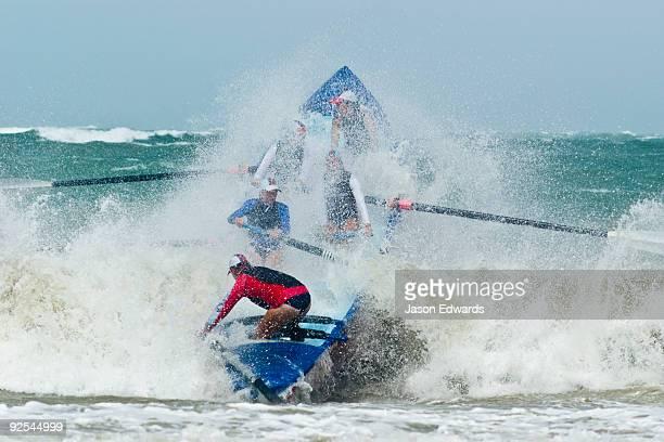 Women row a surf boat through raging seas at the Australian Titles.