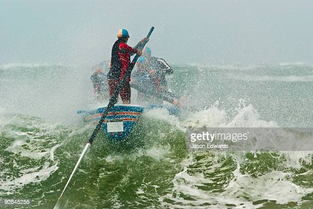 A surf boat crests the top of a green wave in rough seas in a race.