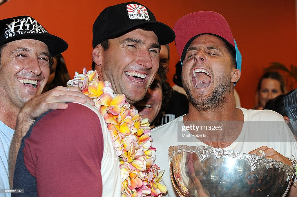 Australian surfer Joel Parkinson is congratulated by Paul Fisher (R) as he arrives home at the Gold Coast airport on December 19, 2012 on the Gold Coast, Australia. Parkinson won the Pipeline Masters and his first ASP World Title on Monday.