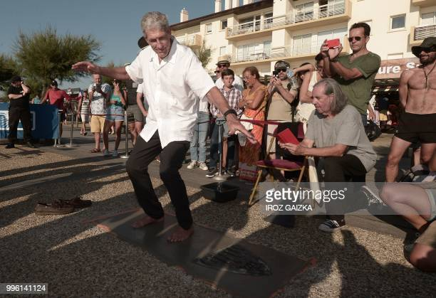 Australian surfer Nat Young leaves his footprint cement slab as he takes part in the inauguration of the Anglet Surf Avenue with other surfers from...