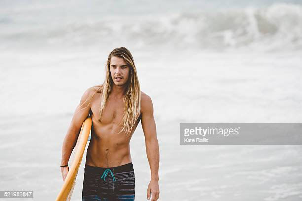 Australian surfer with surfboard, Bacocho, Puerto Escondido, Mexico