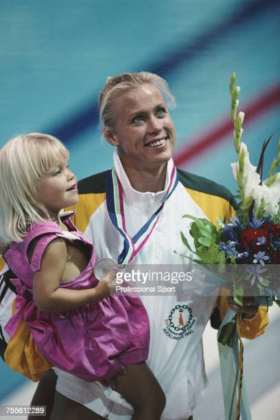 Australian swimmer Lisa Curry pictured holding a young girl on the medal podium at a medal ceremony at the swimminmg pool in Henderson during the...