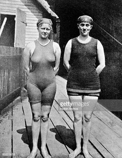 Australian swimmer Mina Wylie and Fanny Durack pose together hands behind their backs and both in swimming suits and caps on a dock probably in...