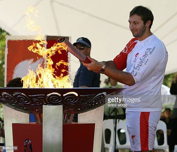 Australian swimming great Ian Thorpe lights the cauldron after arriving as the last torch bearer at the finish of the Beijing Olympic torch relay in...