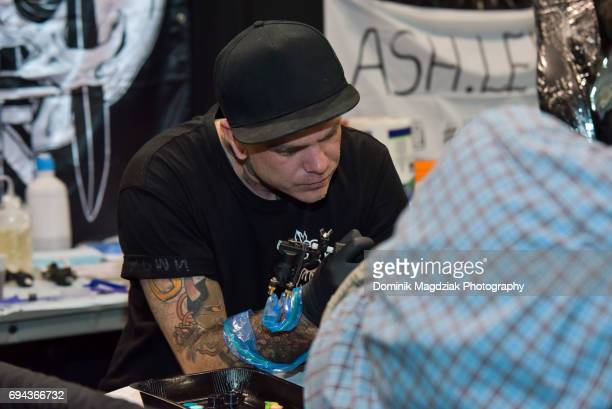 """Australian tattoo artist Stu Pagdin tattoos a man during day one of the """"19th Annual Northern Ink Xposure Tattoo Convention"""" at the Metro Toronto..."""