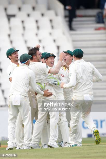 Australian team celebrates the dismissal of South African batsman Faf du Plessis on the first day of the fourth Test cricket match between South...