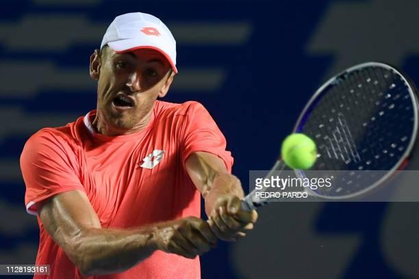 Australian tennis player John Millman returns the ball to US tennis player John Isner during their Mexico ATP 500 Open men's single tennis match in...
