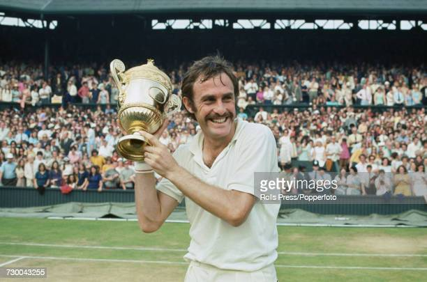 Australian tennis player John Newcombe pictured holding the Gentlemen's Singles Trophy in the air after defeating Stan Smith to win the final of the...