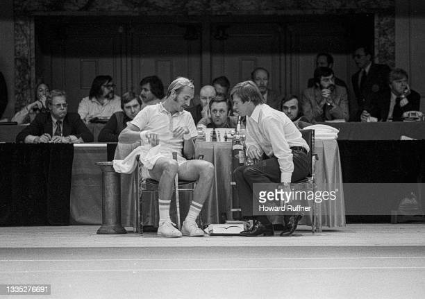 Australian tennis player John Newcombe speaks with an unidentified team representative during a break in a match on the first day of the 62nd Davis...