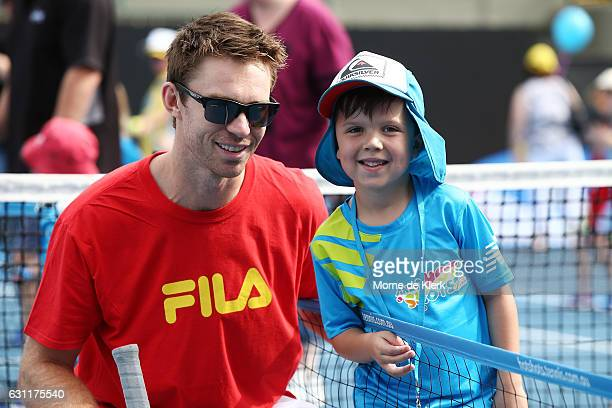 Australian tennis player John Peers poses for a photo with a young player after playing tennis with them at Memorial Drive Tennis court during the...