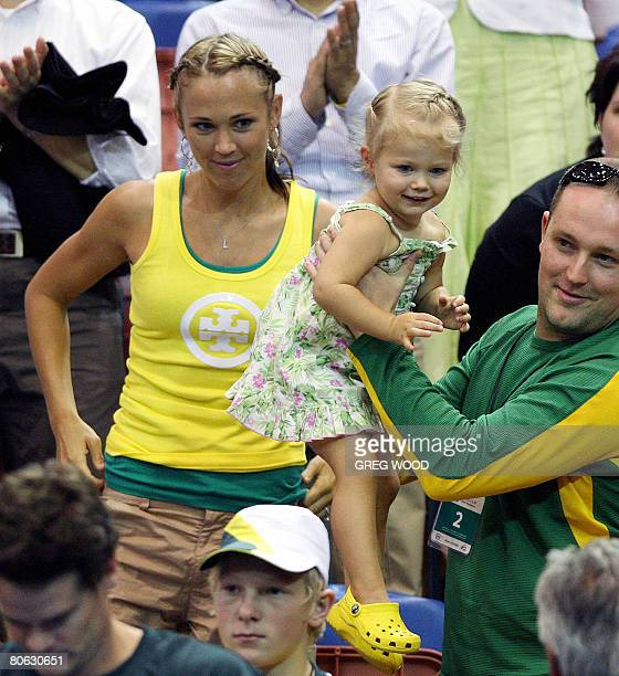 Australian tennis player Lleyton Hewitt's wife Bec watches as her daughter Mia is lifted down onto court for her father after he had just won his...