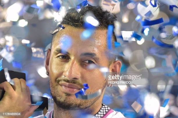 Australian tennis player Nick Kyrgios holds the trophy after defeating German tennis player Alexander Zverev during the Mexico ATP Open men's singles...