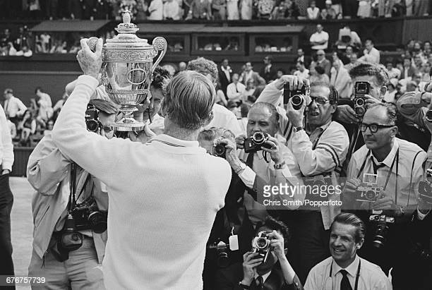 Australian tennis player Rod Laver holds up the Gentlemen's Singles Trophy after defeating fellow Australian tennis player John Newcombe to win the...