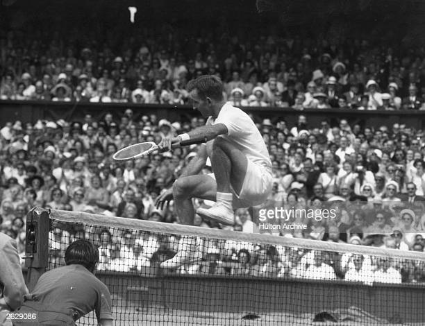 Australian tennis player Rod Laver leaping over the net at Wimbledon after winning the men's singles title on the centre court against America's...