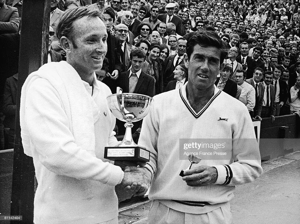 Australian tennis players Rod Laver (left) and Ken Rosewall shake hands as they hold their trophies by the clay court at Roland Garros for the French Tennis Internationals, Paris, France, June 7, 1969.