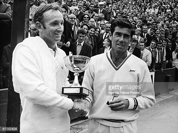 Australian tennis players Rod Laver and Ken Rosewall shake hands as they hold their trophies by the clay court at Roland Garros for the French Tennis...