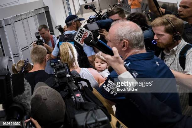 Australian Test cricketer David Warner and his young family wade through a massive media pack at Sydney International Airport on March 29 2018 in...