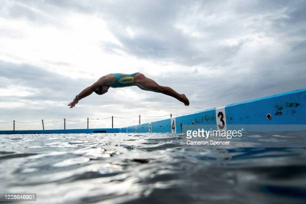 Australian triathlete Emma Jeffcoat dives into the water for a swim training session at Collaroy ocean pool on May 29 2020 in Sydney Australia...