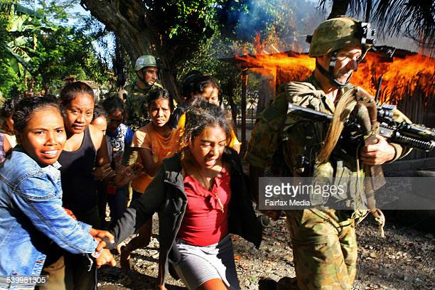 Australian troops lead frightened women and children away from their burning neighbourhood as fighting continued around the streets of Dili and...
