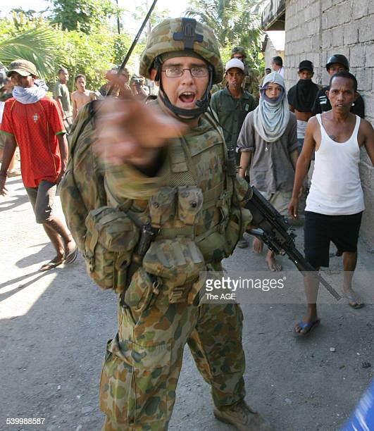 Australian troops try to move warring gangs out of the Komoro district of the East Timorese capital Dili Street fighting has broken out and many...