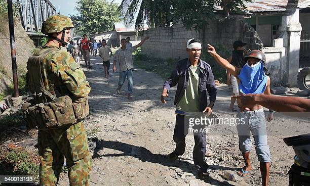 Australian troops try to move warring gangs out of the Komoro district of the East Timorese capital Dili Street fighting has broken out and buildings...