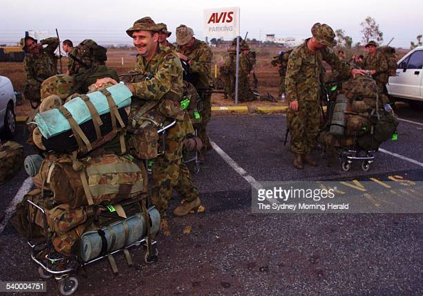 Australian troops use airport trolleys to transport their gear at Darwin Domestic Airport after arriving from Townsville They are headed to the RAAF...