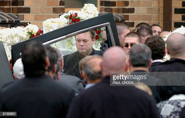 Australian underworld figure and accused drug trafficer Carl Williams helps load the casket of his murdered friend and bodyguard Andrew 'Benji'...