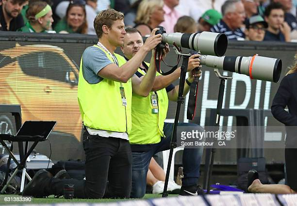 Australian veterinarian and television personality Chris Brown takes photographs on the boundary during the Big Bash League match between the...