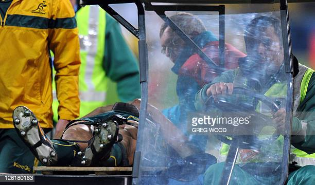 Australian Wallabies center Anthony Faingaa is driven off as he lies in a stretcher after he received an accidental knee to the head which knocked...