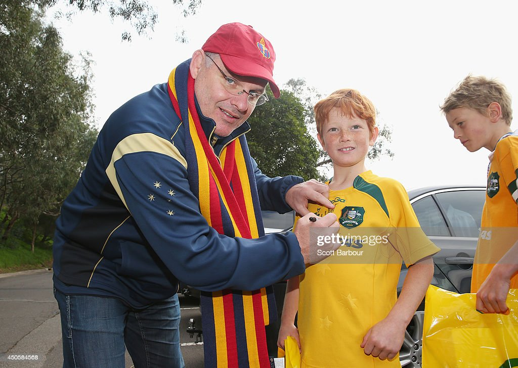 Australian Wallabies coach Ewen McKenzie signs autographs for supporters as he attends St Kevin's College to watch the St. Kevin's College v Scotch College rugby match on June 14, 2014 in Melbourne, Australia.