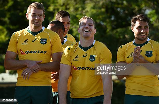 Australian Wallabies rugby player David Pocock laughs with teammates Dean Mumm and Nick Phipps as he takes part in the team photo in Brisbane on June...