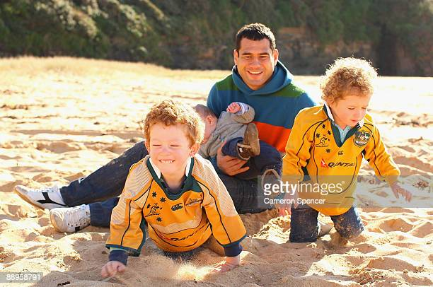 Australian Wallaby player George Smith holds his son Ryker while his other son Wyatt and his daughter Soleil play in the sand at Warriewood beach on...
