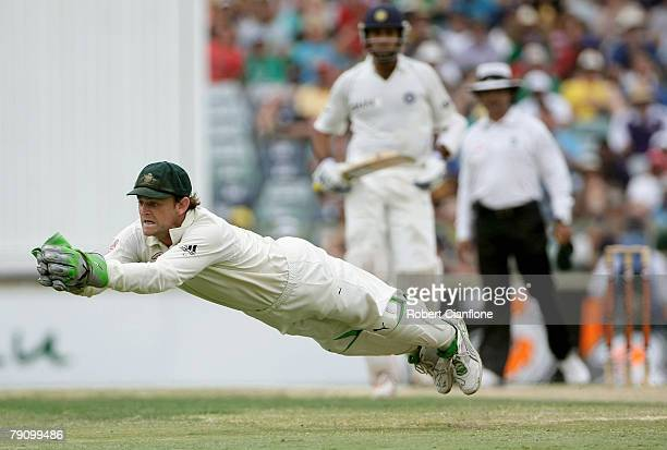 Australian wicket keeper Adam Gilchrist makes a diving catch to dismiss Mahendra Dhoni of India off the bowling of Andrew Symonds during day three of...