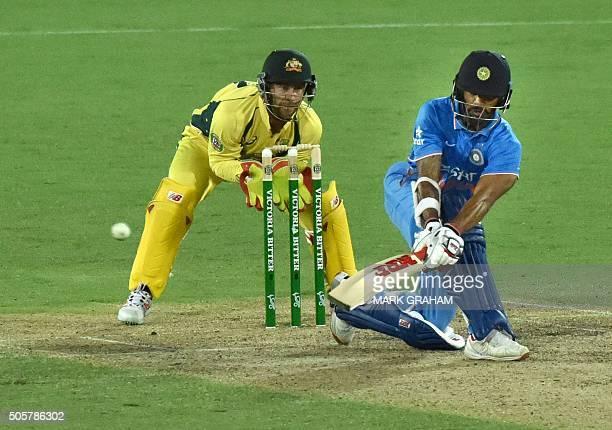 Australian wicketkeeper Matthew Wade watches Indian batsman Shikhar Dhawan play a shot during the fourth oneday international cricket match between...