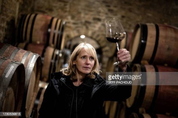 Australian wine merchant Jane Eyre poses for a photograph as she examines a glass of wine, on January 11, 2021 in the Chateau de Blignys cellar in...