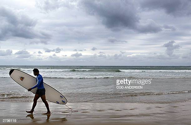 """Australian winger Lote Tuqiri walks along the beach after surfing in Coffs Harbour, 17 November 2003. The """"Wallabies"""" returned to their Rugby 2003..."""