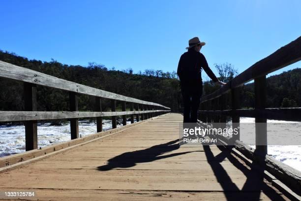 australian woman hiking alone crossing a bridge over the swan river near perth in western australia - rafael ben ari stock-fotos und bilder
