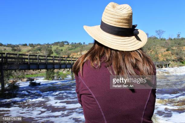 australian woman looking at a wooden walk bridge spanning over the swan river in swan valley near perth in western australia - rafael ben ari - fotografias e filmes do acervo