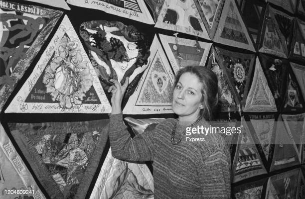 Australian writer Germaine Greer poses pointing at a wall-mounted, hand-stitched quilt, 1st March 1985.