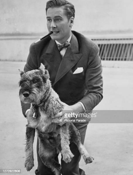Australian-American actor Errol Flynn with his Schnauzer dog Arno, circa 1940.