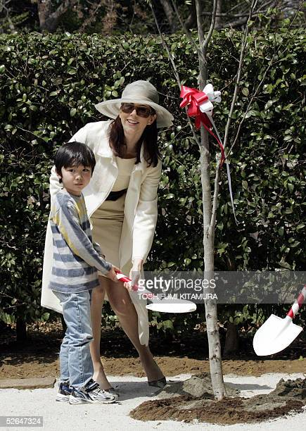 Australian-born Danish Crown Princess Mary helps plant a tree with seven-year-old Yuto Kimura at the Hans Christian Andersen Park in Funabashi city,...