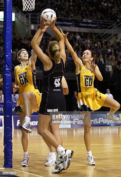 Australians Demelza Fellowes and Liz Ellis looks to block the shot from Silver Fern Irene Van Dyk during the first Fisher and Paykel netball test...