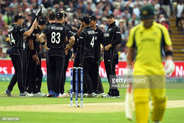 Australia's Aaron Finch leaves the field for eight runs as New Zealand players celebrate during the ICC Champions Trophy match between Australia and...